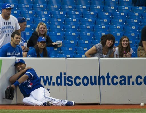 Toronto Blue Jays left fielder Edwin Encarnacion holds his shoulder after dropping the ball on a diving catch on a foul ball hit by Chicago White Sox's Dewayne Wise during the fourth inning of a baseball game in Toronto on Wednesday, Aug. 15, 2012. (AP Photo/The Canadian Press, Nathan Denette)