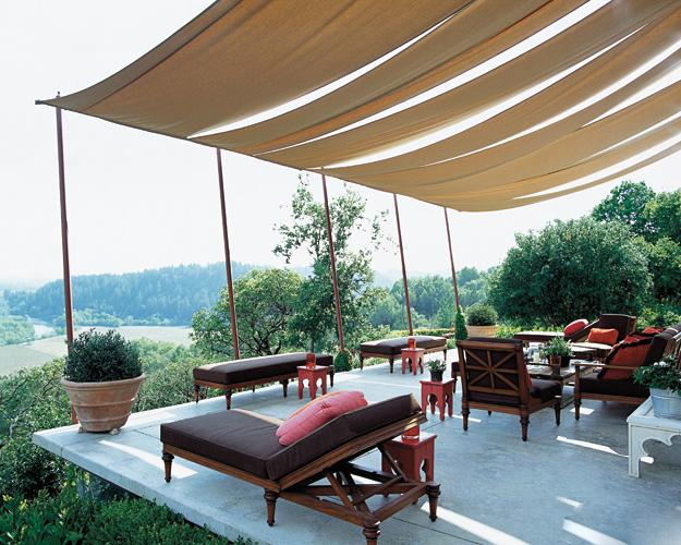 At the home of interior designers Jeffry Weisman and Andrew Fisher in Sonoma County, Calif., the shaded terrace offers a panoramic view of the Russian River Valley. The teak chaise longues, benches, and chairs are by Michael Taylor Designs, and the Moroccan-style red stools add an exotic touch. The fabrics for the upholstery and awning are by Sunbrella. (Photo: Grey Crawford)