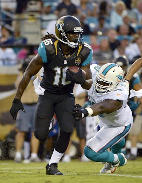 Jacksonville Jaguars wide receiver Denard Robinson (16) runs past Miami Dolphins defensive end Vaughn Martin, right, during the first half of an NFL preseason football game, Friday, Aug. 9, 2013, in Jacksonville, Fla. (AP Photo/Phelan M. Ebenhack)