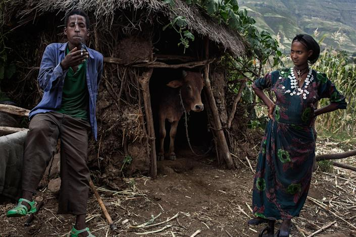 <p>Abaynesh (14) and her husband Tadesse (22) stand together in front of one of the barns next to their home in Gindero, Amhara Ethiopia in October 2016. It is the first time Tadesse smokes and he can't help but cough. Abaynesh and Tadesse are expecting their first child and they declare they won't make their son or daughter go through the same situation they did in being forcibly married. (Photo: José Colón/MeMo) </p>