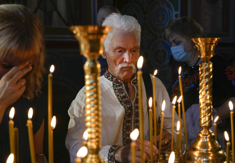 People light candles as they pray in the Mikhailovsky Zlatoverkhy Cathedral (St. Michael's Golden-Domed Cathedral) in Kyiv, Ukraine, Saturday, Aug. 21, 2021. Ecumenical Patriarch Bartholomew I, arrived to Kyiv to mark the 30th anniversary of Ukraine's independence that is celebrated on Aug. 24. (AP Photo/Efrem Lukatsky)