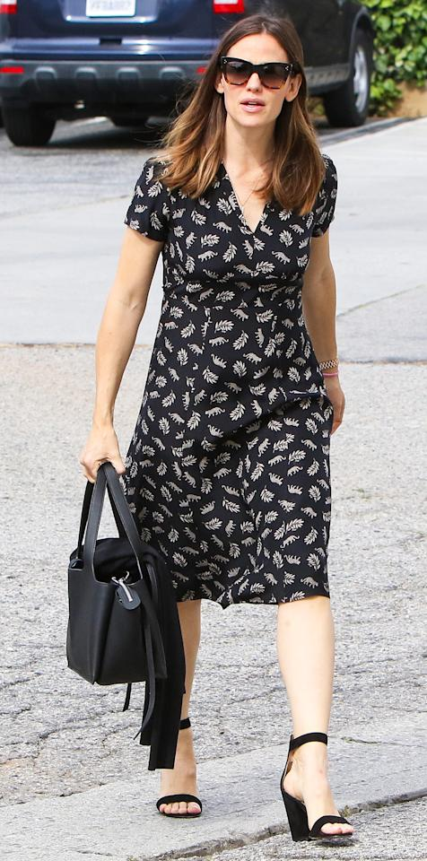 """<p>Garner stepped out on Sunday in a modest black dress with a beige jungle cat and leaf print, which she paired with a matching tote and a set of ankle strap block heel sandals (shop a similar pair <a rel=""""nofollow"""" href=""""https://click.linksynergy.com/fs-bin/click?id=93xLBvPhAeE&subid=0&offerid=293189.1&type=10&tmpid=12371&RD_PARM1=http%3A%2F%2Fwww.barneys.com%2Fproduct%2Fgianvito-rossi-versilia-ankle-strap-sandals-504503151.html%3F&u1=ISJenniferGarnerSSIJApril"""">here</a>).</p>"""