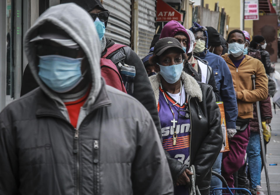 People wait for a distribution of masks and food from the Rev. Al Sharpton in the Harlem neighborhood of New York, after a new state mandate was issued requiring residents to wear face coverings in public due to COVID-19, Saturday, April 18, 2020. (AP Photo/Bebeto Matthews)