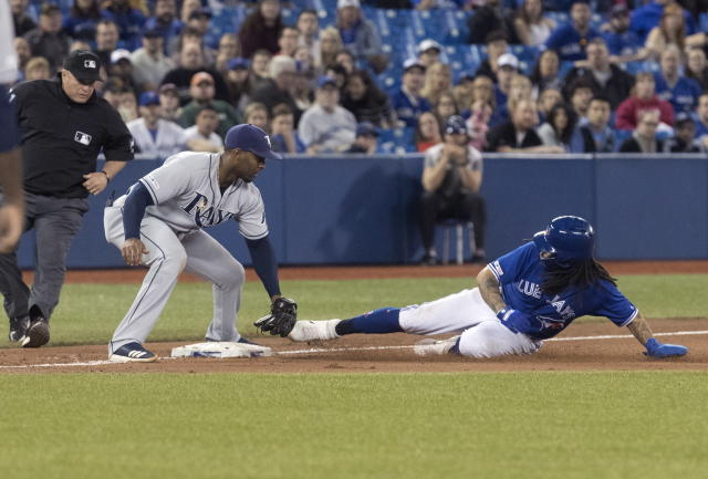 Toronto Blue Jays' Freddy Galvis is out at third trying to advance on a wild pitch as Tampa Bay Rays' Yandy Diaz makes the tag during the seventh inning of a baseball game Friday, April 12, 2019, in Toronto. (Fred Thornhill/The Canadian Press via AP)