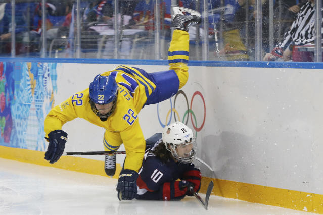 Emma Eliasson of Sweden trips over Meghan Duggan of the United States during the third period of the 2014 Winter Olympics women's semifinal ice hockey game at Shayba Arena, Monday, Feb. 17, 2014, in Sochi, Russia. (AP Photo/Petr David Josek)