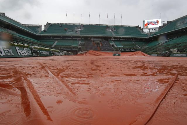 Rain drops splash on the canvas covering center court at the French Open tennis tournament ,Roland Garros stadium, in Paris, France, Wednesday, June 4, 2014. Rain delayed the start of the quarterfinal matches. (AP Photo/Michel Euler)