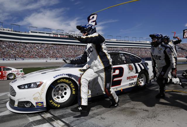 Brad Keselowski pulls out of pit row as his pit crew members finish changing his tires during a NASCAR Sprint Cup Series auto race on Sunday, March 9, 2014, in Las Vegas. Keselowski won the race. (AP Photo/Julie Jacobson)