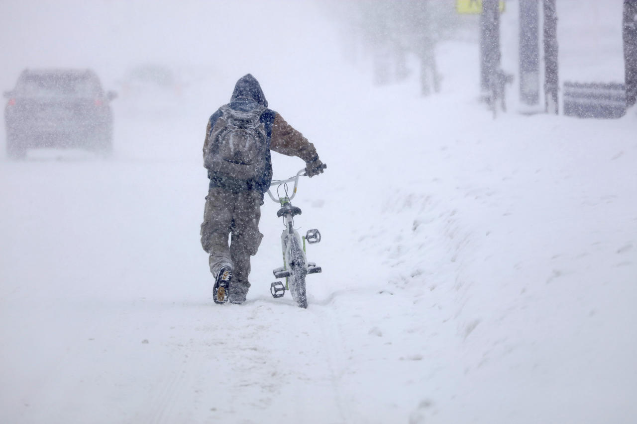 Austin Tauber heads home with his bicycle Wednesday morning, Feb. 20, 2019, in the snow in Anoka, Minn. Forecasters are warning residents in parts of Minnesota and western Wisconsin the advancing winter storm could produce up to 9 inches of snow. (David Denney/Star Tribune via AP)