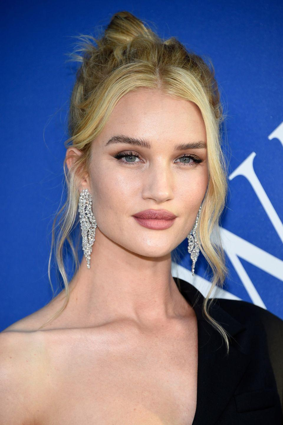 <p>Rosie Huntington-Whiteley often throws her long hair up into a messy high bun, which accentuates her bone structure. To stop it looking too severe, follow her example and leave two tendrils out.</p>