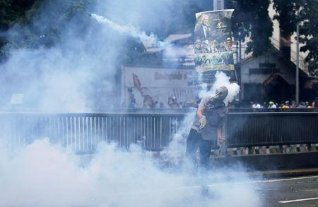 Demonstrator throws back a tear gas canister while clashing with the riot police during a rally. REUTERS/Marco Bello