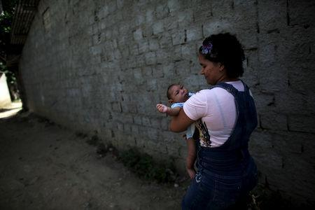 Jackeline Vieira de Souza, 26, holds her four-month-old son Daniel who was born with microcephaly, as they walk toward their house in Olinda, near Recife, Brazil, February 11, 2016. REUTERS/Nacho Doce/Files