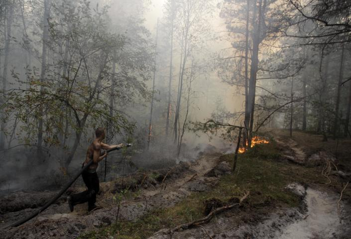 FILE - In this Aug. 7, 2010 file photo, a firefighter tries to stop a forest fire near the village of Verkhnyaya Vereya in Nizhny Novgorod region, some 410 km (255 miles) east of Moscow. Twenty-first century disasters such as killer heat waves in Europe, wildfires in the United States, droughts in Australia and deadly flooding in Mozambique, Thailand and Pakistan highlight how vulnerable humanity is to extreme weather, says a massive new report from a Nobel Prize-winning group of scientists released early Monday, March 31, 2014. (AP Photo/Alexander Zemlianichenko Jr., File)