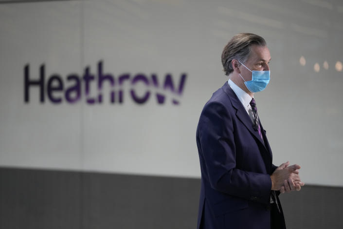 The CEO of Heathrow Airport John Holland-Kaye gives a television interview at Terminal 5 of Heathrow Airport in London, Monday, Aug. 2, 2021. Travelers fully vaccinated against coronavirus from the United States and much of Europe were able to enter Britain without quarantining starting today, a move welcomed by Britain's ailing travel industry. (AP Photo/Matt Dunham)
