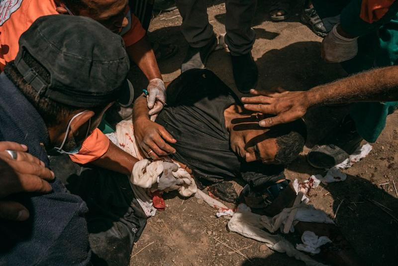 Paramedics assist a man who was injured in the chest and arms by Israeli troops along the Gaza border.