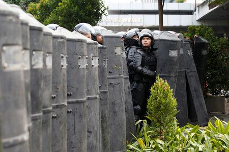 A mobile brigade (Brimob) police officer stands guard at a barricade during a protest near the Election Supervisory Agency (Bawaslu) headquarters in Jakarta