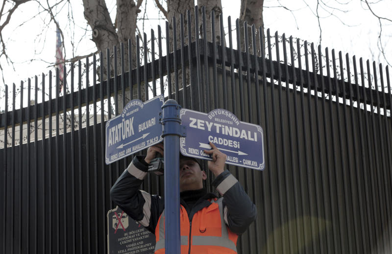 """An Ankara municipality worker fixes the new street sign, """"Olive Branch Street"""" in Turkish, named after Turkey's military operation to drive out the Syrian Kurdish militia of an enclave in northwest Syria, in Ankara, Turkey, Monday, Feb. 19, 2018. Municipality workers on Monday took down the street sign for Nevzat Tandogan Street where the U.S. Embassy is located and replaced it with one that reads """"Olive Branch Street."""" The Embassy's flag was at half-staff in respect for the Florida school shooting victims. (AP Photo/Burhan Ozbilici)"""