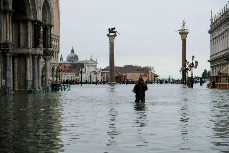 A man stands in water at the flooded St Mark's Square during exceptionally high water levels in Venice