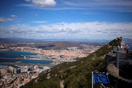 FILE PHOTO: A general view shows the Spanish city of La Linea de la Concepcion (rear) and the tarmac of the Gibraltar International Airport (bottom L) while tourists stand on the top of the Rock (R) next to the European Union flag, in the British overseas territory of Gibraltar, September 14, 2016. REUTERS/Jon Nazca/File Photo