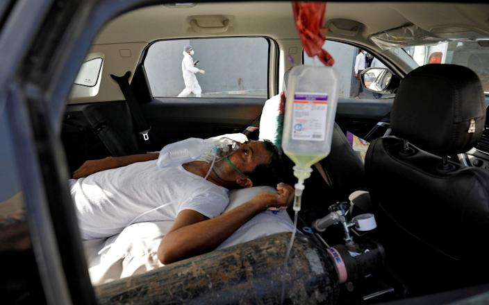 A patient with breathing problems is seen inside a car while waiting to enter a COVID-19 hospital  - REUTERS/Amit Dave