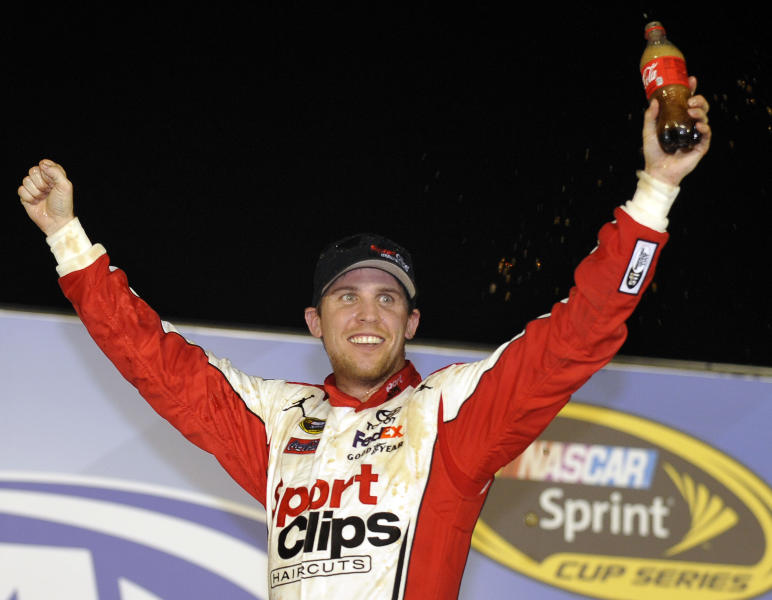 Denny Hamlin celebrates in Victory Lane after winning the NASCAR Sprint Cup Series auto race at Atlanta Motor Speedway, Sunday, Sept. 2, 2012, in Hampton, Ga. (AP Photo/Rainier Ehrhardt)
