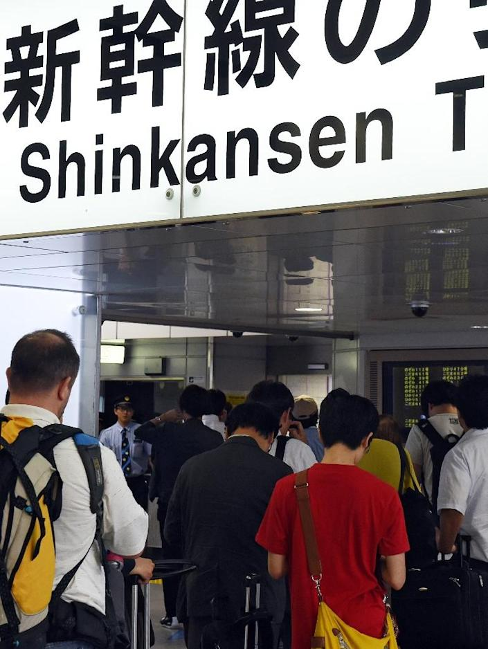 Passengers wait for information outside the shinkansen bullet train ticket barrier at Tokyo station on June 30, 2015 after service was disrupted due to an apparent suicide attempt on board (AFP Photo/Toshifumi Kitamura)