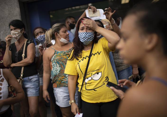 People out of work wait outside a government-run bank having technical problems to distribute their aid money amid the new coronavirus pandemic's affect on the economy in Rio de Janeiro, Brazil, Tuesday, April 28, 2020. (AP Photo/Silvia Izquierdo)