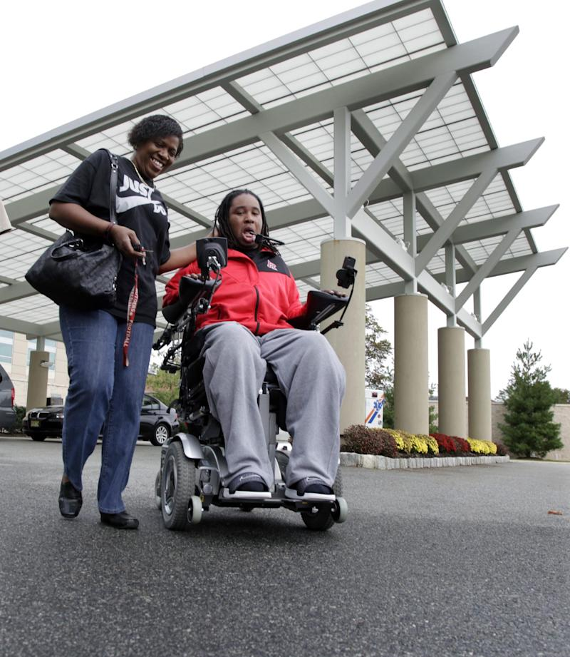 FILE - In this photo taken Wednesday, Oct. 12, 2011, former Rutgers football player Eric LeGrand, right, and his mother Karen LeGrand leave the Kessler Institute for Rehabilitation in West Orange, N.J. The mother of paralyzed Rutgers football player Eric LeGrand is reaching out to the parents of the Tulane player whose spinal cord was severely injured during a game. Karen LeGrand tells The Associated Press on Tuesday, Sept. 11, 2012,  she and her son will make themselves available to Devon Walker and his family in any way they can. (AP Photo/Mel Evans, File)