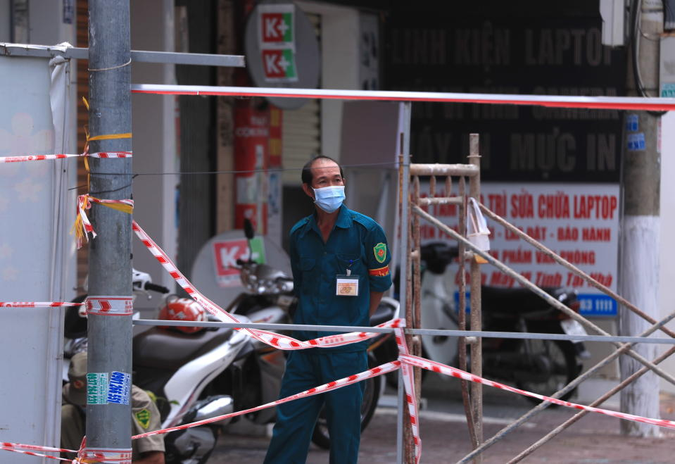 A security officer guards a road block in Vung Tau, Vietnam, Monday, Sept. 13, 2021. The roadblocks and barricades make the streets of this southern Vietnamese city look like they did during the war that ended almost 50 years ago. But this time, the battle is being fought against the rampaging coronavirus.(AP Photo/Hau Dinh)