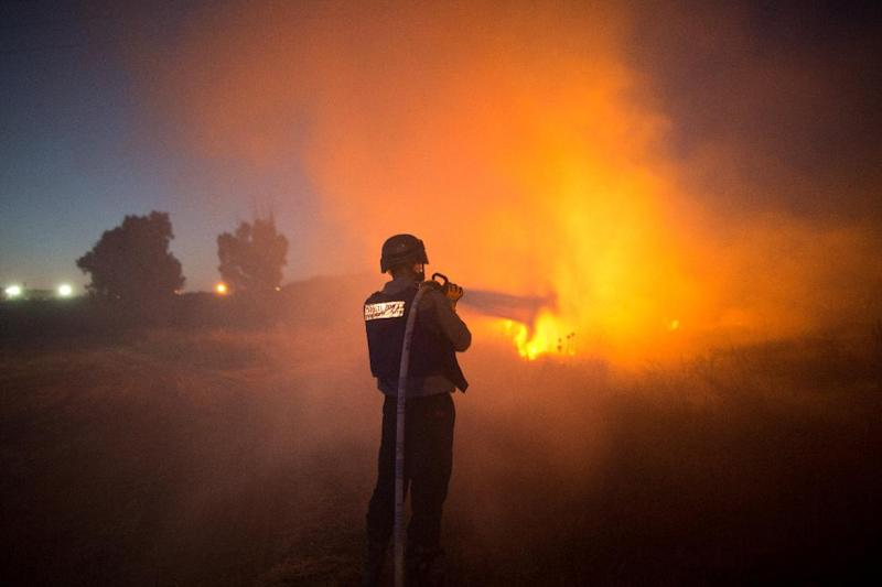An Israeli firefighter extinguishes fire after rockets fired by Palestinian militants from the Gaza strip hit a field near the southern Israeli city of Sderot on August 20, 2014 (AFP Photo/Menahem Kahana)