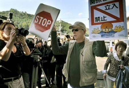 """Ric O'Barry (C), a U.S. dolphin conservationist who appeared in the Oscar-winning documentary """"The Cove"""", holds signs to protest against dolphin hunting in Taiji town, Wakayama Prefecture, in this Kyodo picture taken November 2, 2010.  Mandatory credit REUTERS/Kyodo"""