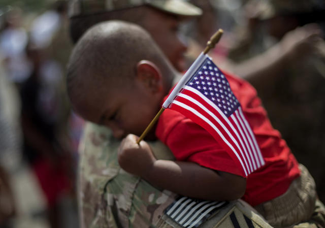 <p>Tyson Hicks, 2, holds an American flag while embraced by his father Sgt. 1st Class Gabriel Hicks upon returning from a deployment to Afghanistan with the Georgia National Guard's 48th Infantry Brigade Combat Team, Sept. 16, 2014, in Macon, Ga. (AP Photo/David Goldman) </p>