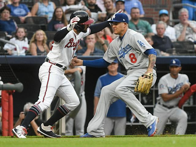 Los Angeles Dodgers shortstop Manny Machado (8) tags out Atlanta Braves' Nick Markakis in a rundown along the third base line during the second inning of a baseball game Friday, July 27, 2018, in Atlanta. (AP Photo/John Amis)