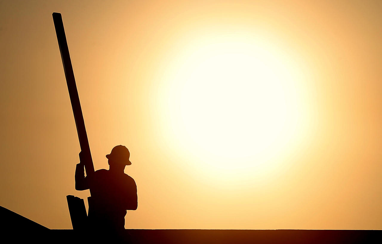 A construction worker is shown atop a roof at sunrise to beat daytime high temperatures, Thursday, June 27, 2013 in Queen Creek, Ariz. Excessive heat warnings will continue for much of the Desert Southwest as building high pressure triggers major warming in eastern California, Nevada, and Arizona. Dangerously hot temperatures are expected across the Arizona deserts throughout the week with a high of 118 by Friday. (AP Photo/Matt York)