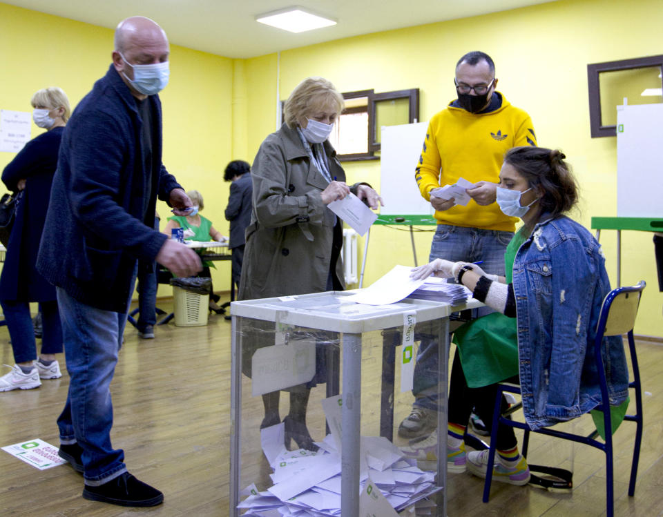 Voters wearing face masks to help curb the spread of the coronavirus, cast their ballots at a polling station during the parliamentary elections in Tbilisi, Georgia, Saturday, Oct. 31, 2020. The hotly contested election between the Georgian Dream party, created by billionaire Bidzina Ivanishvili who made his fortune in Russia and has held a strong majority in parliament for eight years, and an alliance around the country's ex-President Mikheil Saakashvili, who is in self-imposed exile in Ukraine. (AP Photo/Shakh Aivazov)