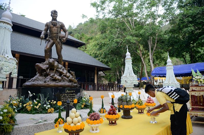 "A member of the ""Wild Boars"" football team places flowers in front of a statue of Saman Gunan, the Thai navy diver who died during the rescue of the team from the Tham Luang cave (AFP Photo/Jittrapon KAICOME)"