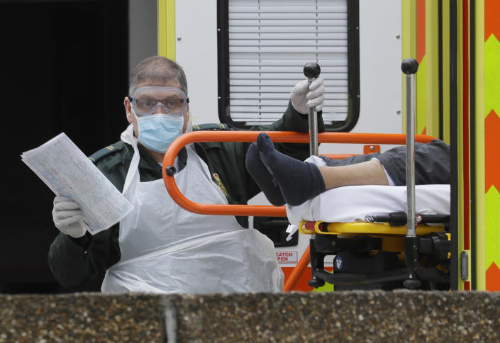 FILE - In this Tuesday, March 31, 2020 file photo a patient is helped from an ambulance as they arrive at St Thomas' Hospital, one of may hospitals that are in the front line of the coronavirus outbreak, in London. (AP Photo/Kirsty Wigglesworth)