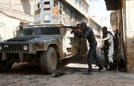Iraqi Federal Police fires his rifle at Islamic State fighters' positions at Bab al Jadid district in the old city of Mosul