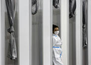 """A medical worker wearing protective gear waits for people to receive the COVID-19 vaccine, at Belgrade Fair makeshift vaccination center in Belgrade, Serbia, Tuesday, Feb. 9, 2021. China is ready to consider """"vaccine cooperation"""" with Central and Eastern European countries, President Xi Jinping said Tuesday in a meeting held by video link with European leaders. Serbia has received 1 million doses of a Chinese-developed coronavirus vaccine and Hungarian and Chinese vaccine developers are cooperating. (AP Photo/Darko Vojinovic)"""