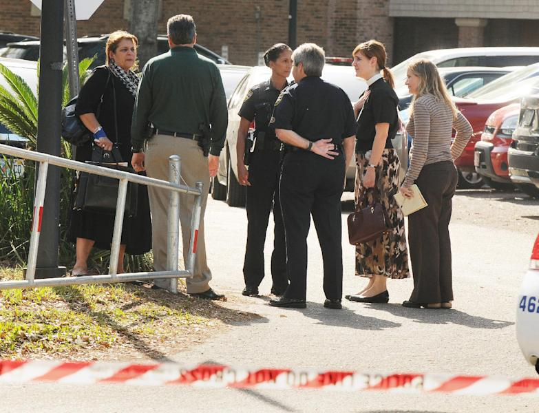 State attorney Angela Corey, left, speaks with investigators and faculty near the back entrance of Episcopal High School Tuesday, March 6, 2012 in Jacksonville, Fla. after a shooting at the school. Authorities say Dale Regan, head of the Episcopal School of Jacksonville, was shot and killed Tuesday by a recently terminated employee who also was found dead. (AP Photo/The Florida Times-Union, Bob Self)