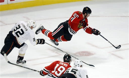 Chicago Blackhawks left wing Brandon Saad (20) shoots and scores past Anaheim Ducks defenseman Toni Lydman (32), of Finland, as Blackhawks' Jonathan Toews (19) and Ducks' Emerson Etem watch during the second period of an NHL hockey game, Tuesday, Feb. 12, 2013, in Chicago. (AP Photo/Charlie Arbogast)