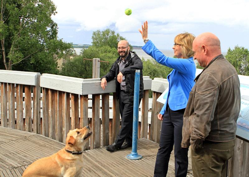"Former U.S. Rep. Gabrielle Giffords, D-Ariz., tosses a ball for her 2-year-old dog, Nelson, with husband, former astronaut Mark Kelly, at an overlook of Cook Inlet in Resolution Park on Tuesday, July 2, 2013, in Anchorage, Alaska. Giffords and Kelly are in Alaska as part of a seven-state ""Rights and Responsibilities Tour"" urging members of Congress to expand background checks on gun sales. Giffords, who survived a 2011 assassination attempt, and Kelly founded Americans for Responsible Solutions. (AP Photo/Dan Joling)"