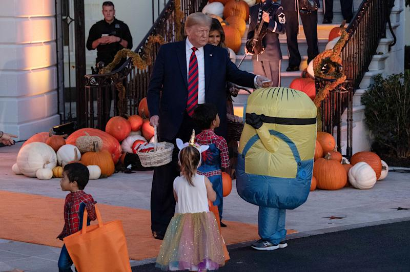 President Donald Trump and First Lady Melania Trump hand out candy for children at a Halloween celebration at the White House. (Photo: Nicholas Kamm via Getty Images)