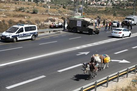 Woman rides a donkey as she passes the scene of what Israeli military said is a car-ramming attack near the settlement of Elazar in the Israeli-occupied West Bank