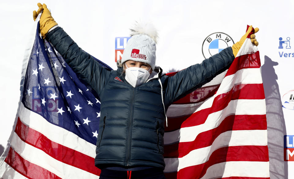Bobsleigh pilot Kaillie Humphries of the United States celebrates on the podium after taking first place in the women's monobob race at the Bobsleigh and Skeleton World Championships in Altenberg, Germany, Sunday, Feb.14, 2021. (AP Photo/Matthias Schrader)