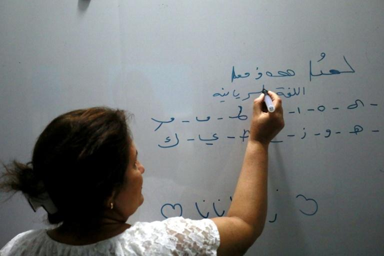 Teacher Samira Hanna writes on a board in Syriac at a school in the northeastern Syrian city of Qamishli