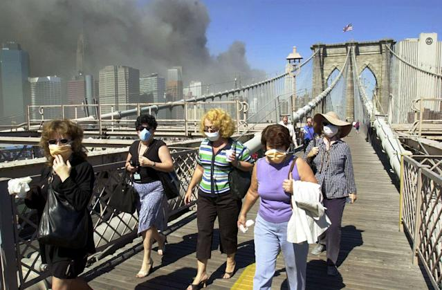 <p>Women wearing dust masks flee across the Brooklyn Bridge from Manhattan to Brooklyn following the collapse of both World Trade Center towers, Sept. 11, 2001, in New York. The towers previously loomed tall in the skyline behind. (Photo:Mark Lennihan/AP) </p>