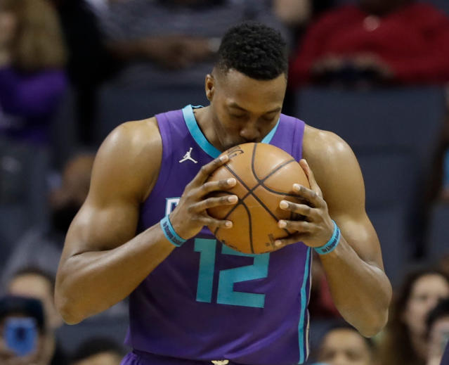 FILE - In this April 8, 2018, file photo, Charlotte Hornets' Dwight Howard (12) kisses the basketball before the start of an NBA basketball game against the Indiana Pacers in Charlotte, N.C. A person familiar with the situation says the Charlotte Hornets have agreed to trade eight-time All-Star center Dwight Howard to the Brooklyn Nets for center Timofey Mozgov and two future second-round draft picks. The person spoke to The Associated Press on condition of anonymity Wednesday, June 20, 2018, because the teams have not announced the trade and the league has not yet approved it. (AP Photo/Chuck Burton, File)