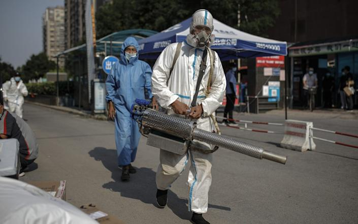 Workers carry out disinfection operations in a residential area near locked-down areas due to the outbreak in Beijing - STRINGER/EPA-EFE/Shutterstock