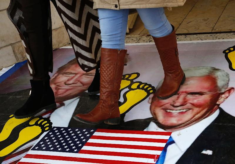 Palestinians walking on a poster bearing images of US President Donald Trump and Vice President Mike Pence during a demonstration at the al-Quds Open University in Dura village on the outskirts of the West Bank town of Hebron on December 13, 2017