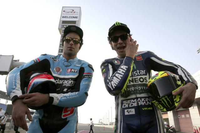 Yamaha MotoGP rider Valentino Rossi (R) of Italy poses with compatriot Danilo Petrucci of Ioda Racing Project before the free practice session of the MotoGP World Championship at the Losail International circuit in Doha March 20, 2014. REUTERS/Fadi Al-Assaad (QATAR - Tags: SPORT MOTORSPORT)